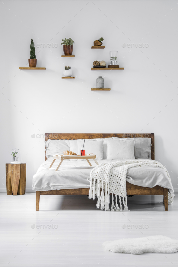 Front view of a wooden framed double bed with linen, pillows and - Stock Photo - Images
