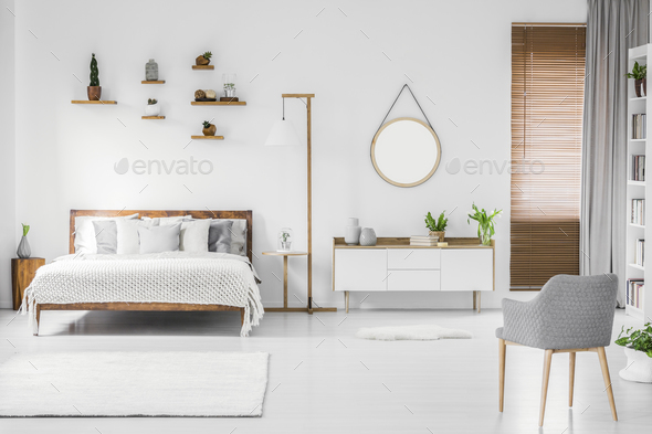 Spacious designer white bedroom interior with wooden bed with be - Stock Photo - Images