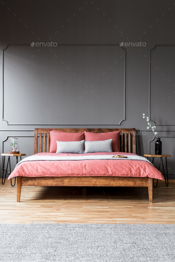 A large bed standing in a dark bedroom interior between bedside - Stock Photo - Images