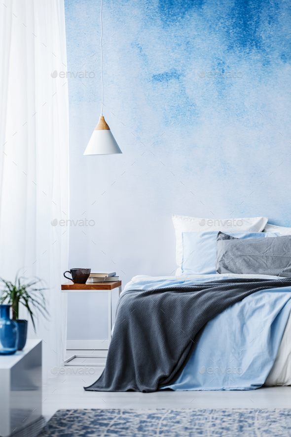 Blue and grey blanket on bed against ombre wall in bedroom inter - Stock Photo - Images