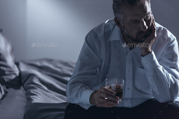 Close-up of a man with midlife crisis sitting on a bed with one - Stock Photo - Images