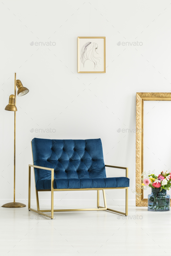 A luxurious, navy blue armchair, golden elements,framed art and - Stock Photo - Images