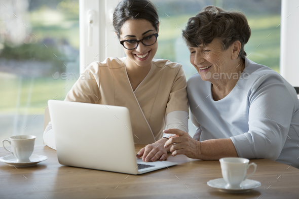 Smiling assistant teaching elderly woman - Stock Photo - Images