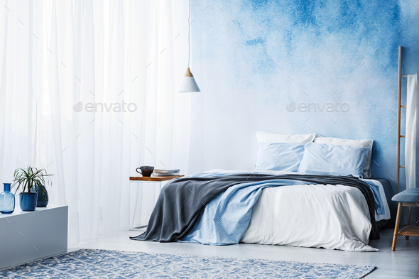 Plant on white cupboard in spacious blue bedroom interior with g - Stock Photo - Images