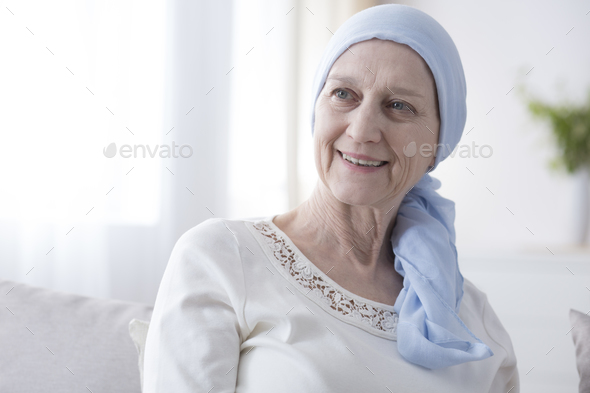 Happy woman in cancer headscarf - Stock Photo - Images