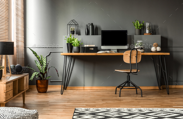 Real photo of a dark interior with wooden desk, chair and comput - Stock Photo - Images