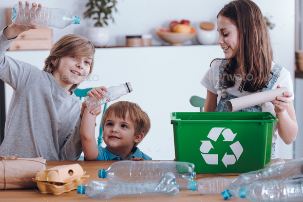 Smiling children segregating plastic bottles - Stock Photo - Images