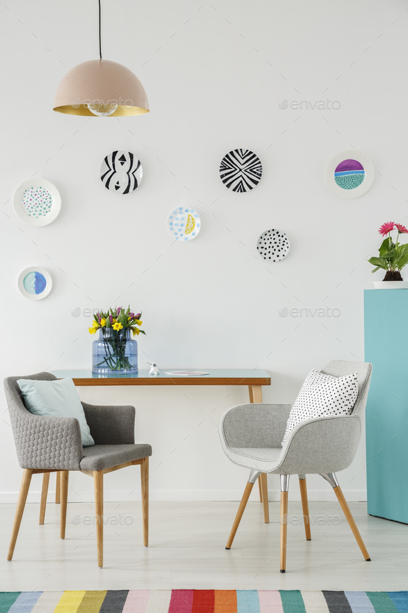 Creative living room interior with plates on the wall, table, gr - Stock Photo - Images