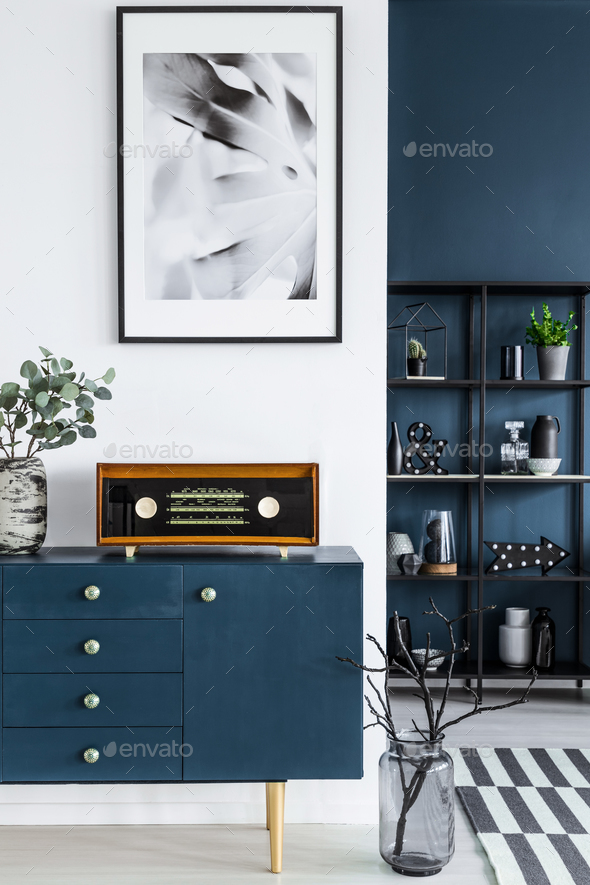 Close-up of a painting, blue cabinet, retro radio and glass vase - Stock Photo - Images