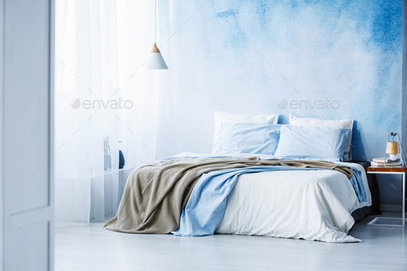 Yellow and blue bedding on white bed in minimal bedroom interior - Stock Photo - Images