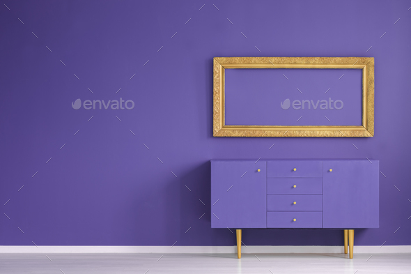 Real photo of a golden frame hanging above a purple cupboard in - Stock Photo - Images