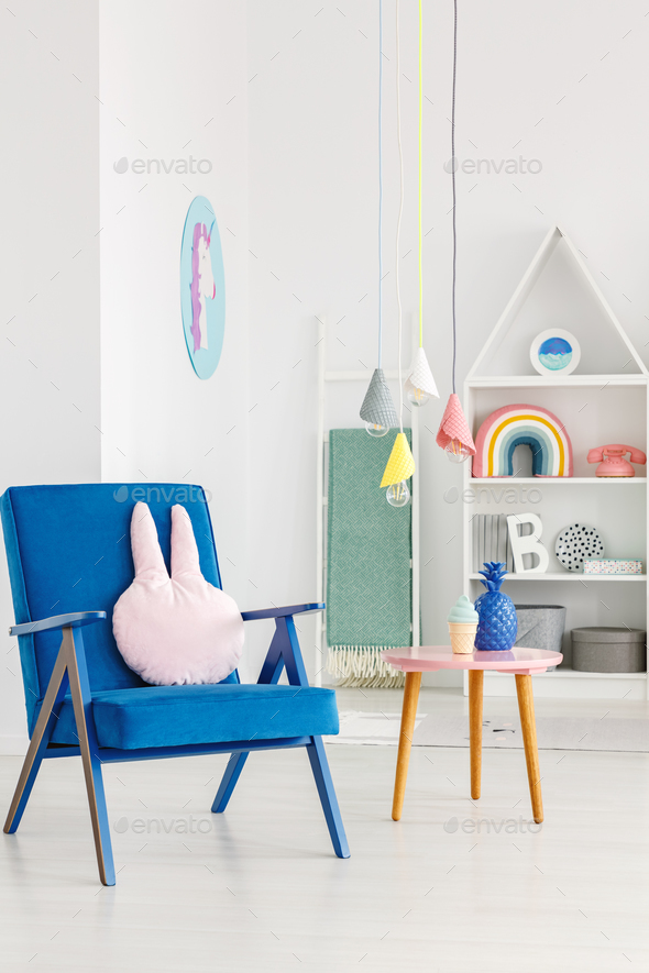 Navy blue armchair with a rabbit pillow next to a table and whit - Stock Photo - Images