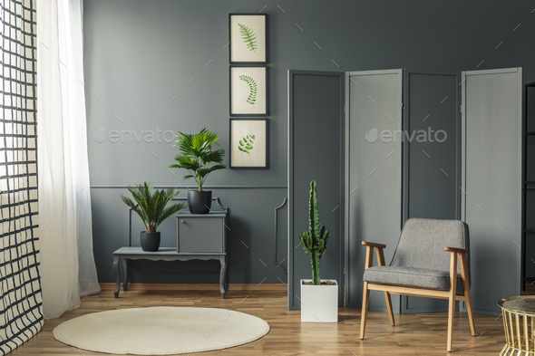 A chair standing in front of a decorative, grey screen next to a - Stock Photo - Images