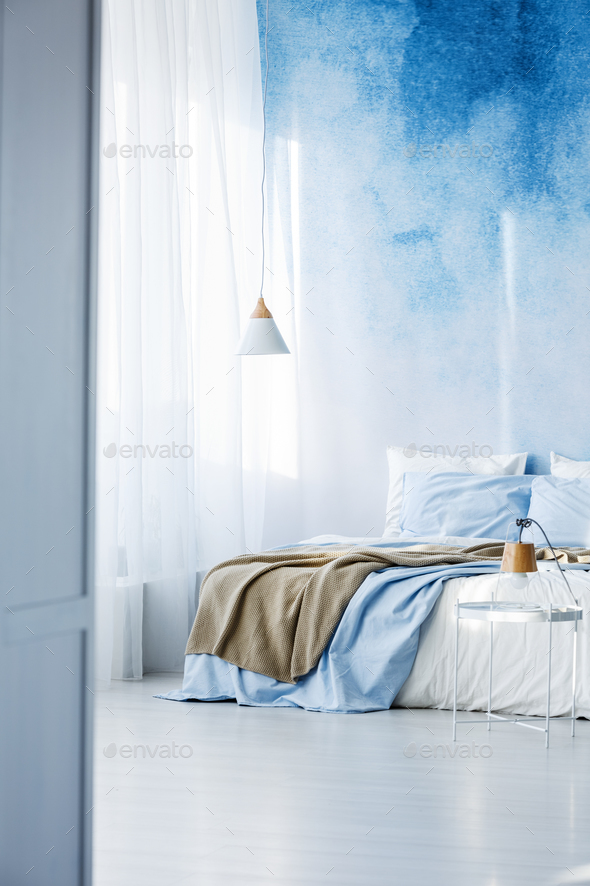 Bright bedroom interior with double bed, beige blanket and ombre - Stock Photo - Images