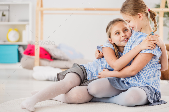 Sisters wearing blue shirts hugging - Stock Photo - Images