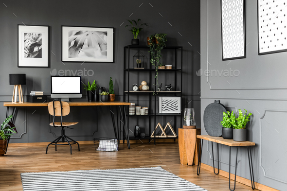 Black rack with decorations standing next to a wooden chair and - Stock Photo - Images