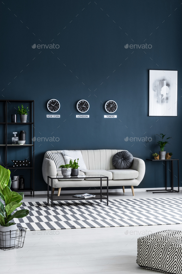 White sofa, coffee table, clocks on the grey wall and striped ru - Stock Photo - Images