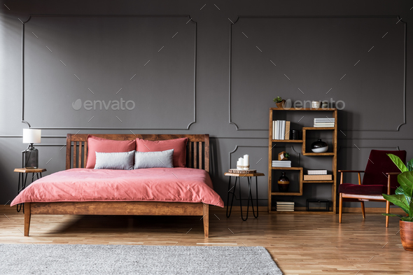 Real photo of a spacious bedroom interior with pink bed standing - Stock Photo - Images