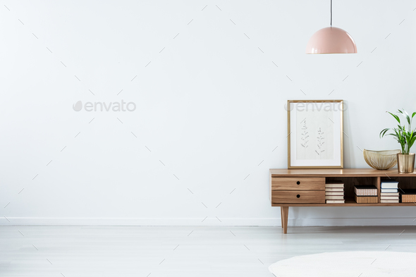 Pink lamp above wooden sideboard - Stock Photo - Images