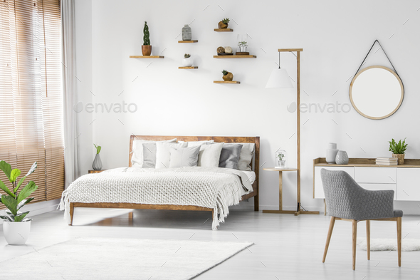 Front view of a bright natural bedroom interior with wooden bed - Stock Photo - Images