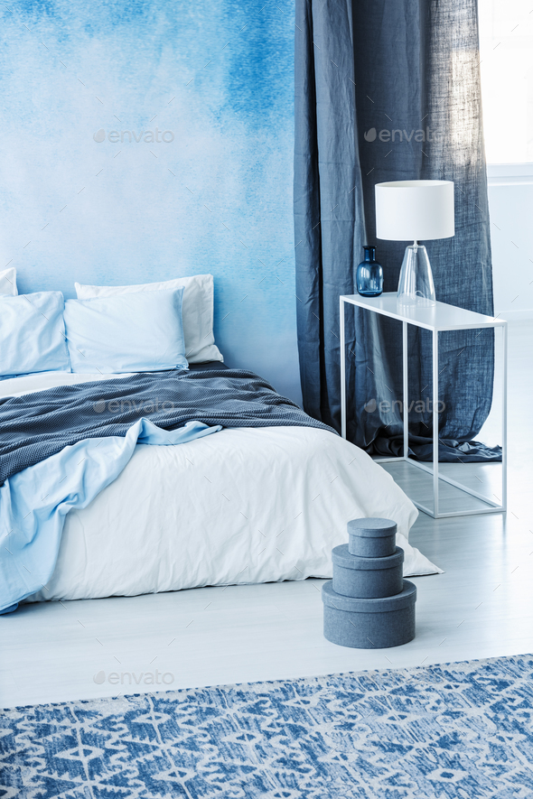 Patterned carpet and grey boxes next to bed with blue bedding in - Stock Photo - Images