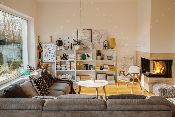 White Scandinavian living room interior with fireplace, posters, - Stock Photo - Images
