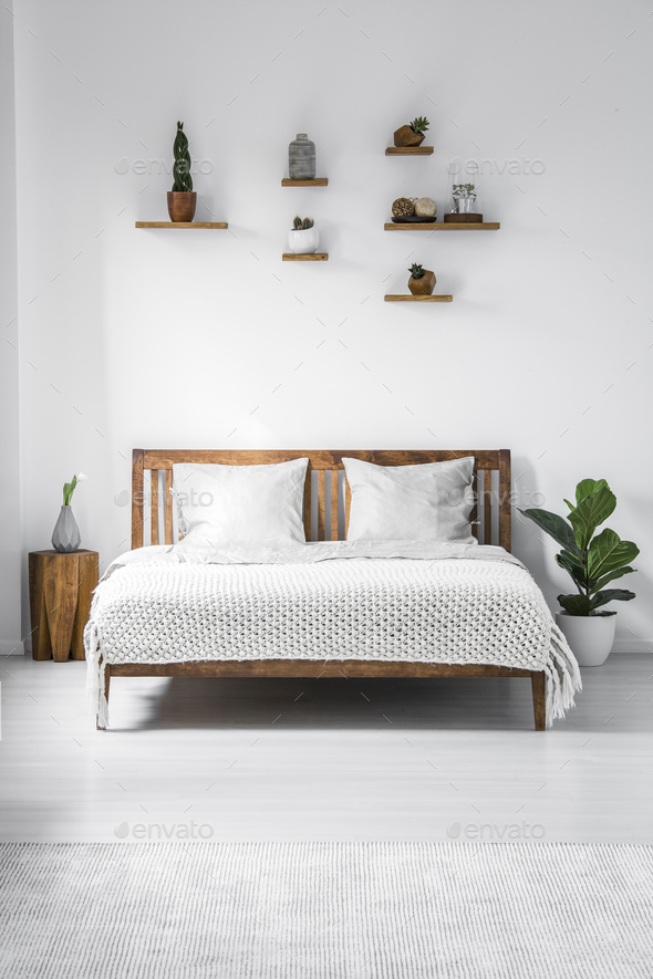 Wooden framed double bed with two pillows and a blanket, and sma - Stock Photo - Images
