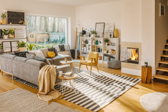 Blanket thrown on grey corner sofa in white living room interior - Stock Photo - Images