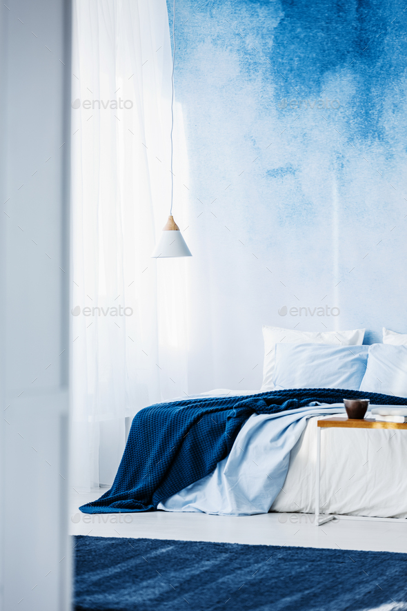 White lamp above bed with navy blue blanket in bedroom interior - Stock Photo - Images