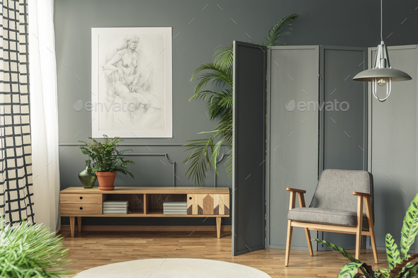 Retro armchair against a gray screen next to a drawing hanging o - Stock Photo - Images