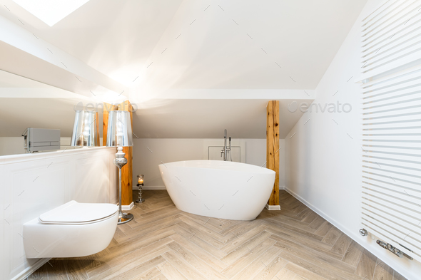 White attic bathroom with bathtub - Stock Photo - Images