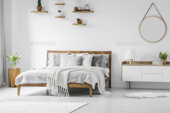 Comfortable big wooden framed bed with linen, pillows and blanke - Stock Photo - Images