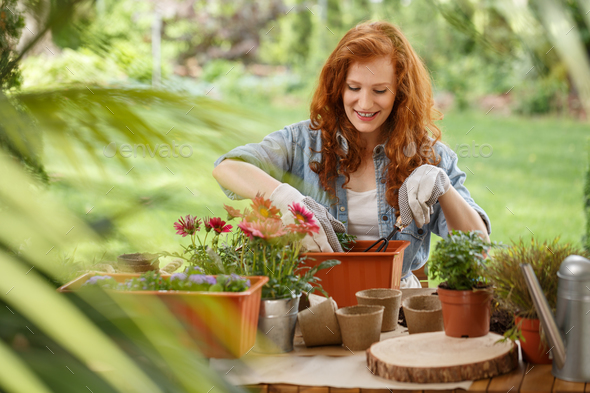 Woman pouring soil into container - Stock Photo - Images
