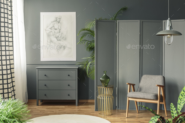 Dark, gray living room interior with a sketch hanging above a wo - Stock Photo - Images