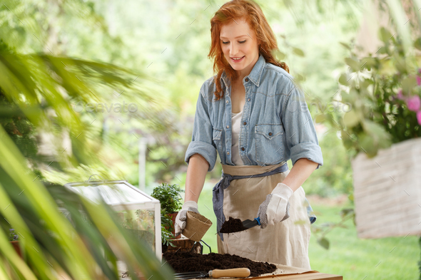 Happy housewife exaggaterating flowers - Stock Photo - Images