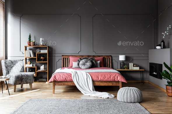 Real photo of a cozy bedroom interior with wooden bed in the mid - Stock Photo - Images