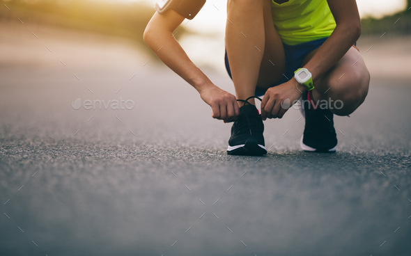 Runner tying shoelace before run - Stock Photo - Images