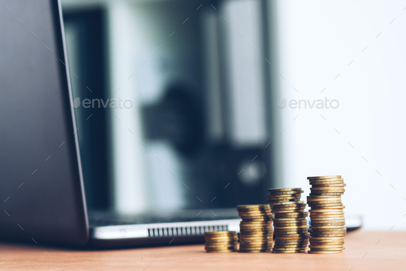 Stacked money coins and laptop computer - Stock Photo - Images