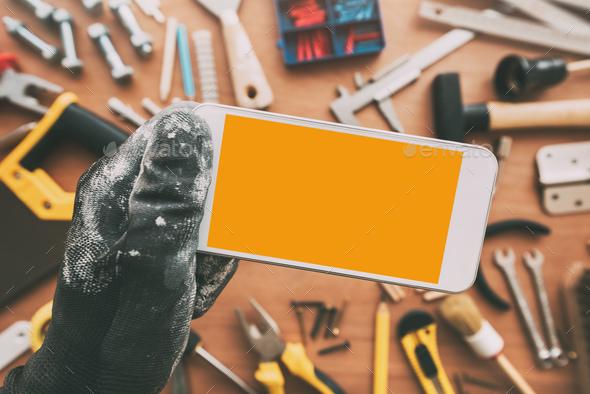 Repairman smart phone app, repairman holding mobile phone in han - Stock Photo - Images