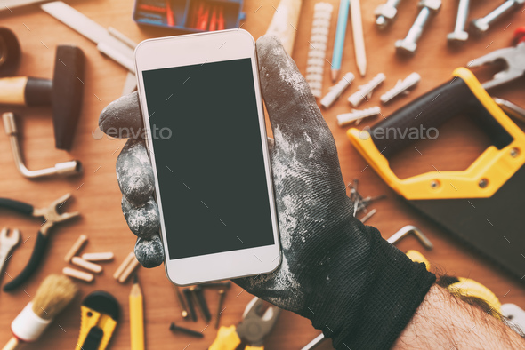 Smart phone app for handyman, repairman holding mobile phone - Stock Photo - Images