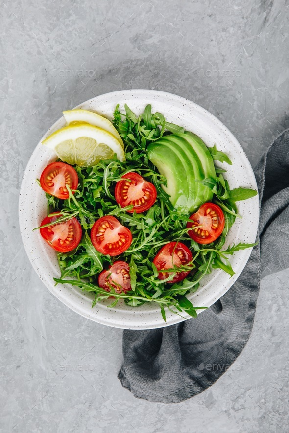 Green salad with leaves of arugula, tomatoes and avocado. - Stock Photo - Images