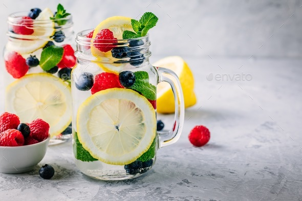Infused detox water with lemon slice, raspberry, blueberry and mint. - Stock Photo - Images