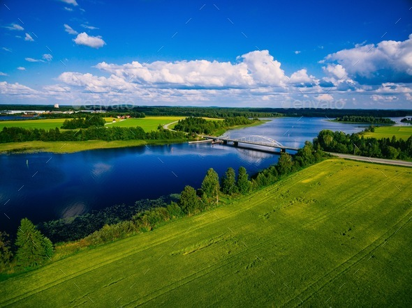 Aerial view on bridge over blue lake in rural Finland countryside with green and yellow fields - Stock Photo - Images