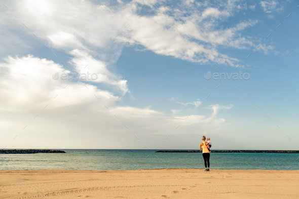 Mother with baby boy enjoying sunrise on a beach - Stock Photo - Images
