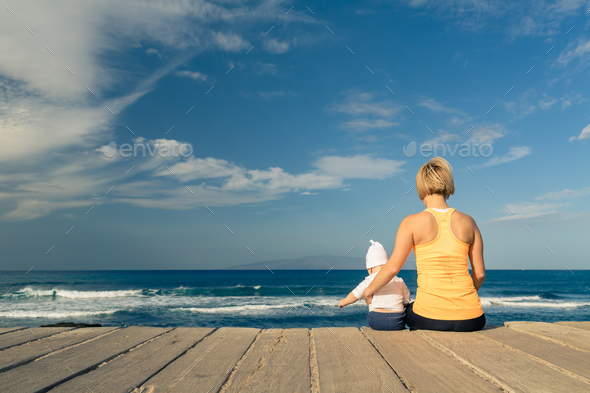 Baby boy playing with mother on the beach, summer day - Stock Photo - Images