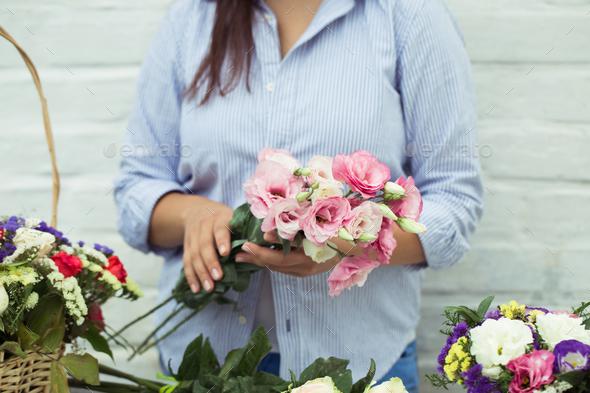 Female florist making beautiful bouquet at flower shop - Stock Photo - Images