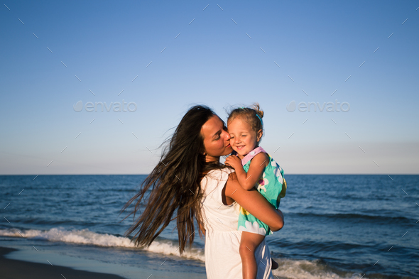 Mather and baby on the sea beach - Stock Photo - Images