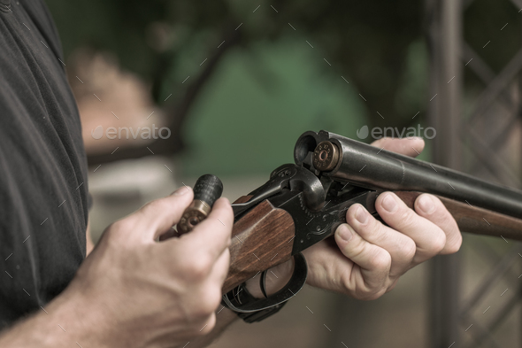 Man charging double-barreled hunting rifle closeup - Stock Photo - Images