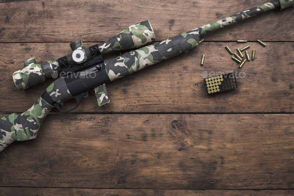 Small caliber 22 long rifle with an optical sight and cartridges in camouflage tape - Stock Photo - Images