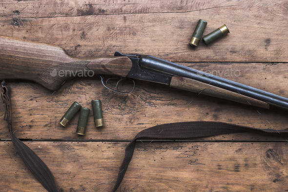 Shotgun with cartridges on a wooden background - Stock Photo - Images